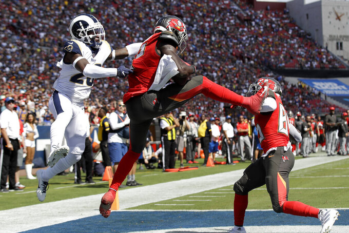 Tampa Bay Buccaneers wide receiver Chris Godwin, middle, scores ahead of Los Angeles Rams defensive back Nickell Robey-Coleman, left, during the first of an NFL football game Sunday, Sept. 29, 2019, in Los Angeles. (AP Photo/Marcio Jose Sanchez)