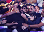 Supporters embrace Dario Sammartino, of Italy, facing away from camera, after he was eliminated at the final table of the World Series of Poker main event, Wednesday, July 17, 2019, in Las Vegas. Sammartino finished the tournament in second place. (AP Photo/John Locher)