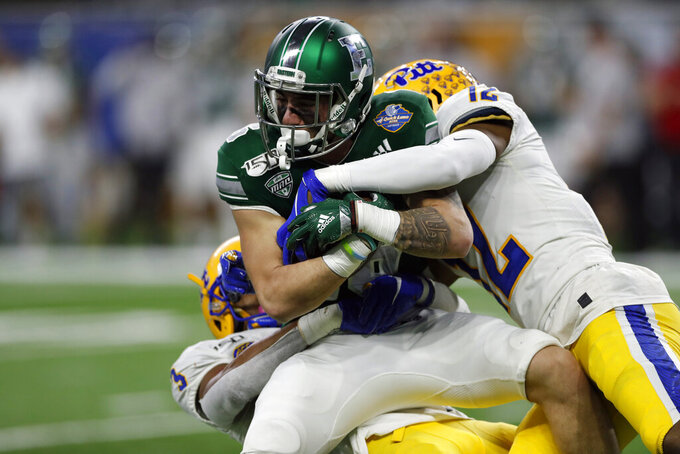 Eastern Michigan wide receiver Hassan Beydoun is tackled by Pittsburgh defensive backs Damar Hamlin, left, and Paris Ford (12) during the first half of the Quick Lane Bowl NCAA college football game Thursday, Dec. 26, 2019, in Detroit. (AP Photo/Carlos Osorio)
