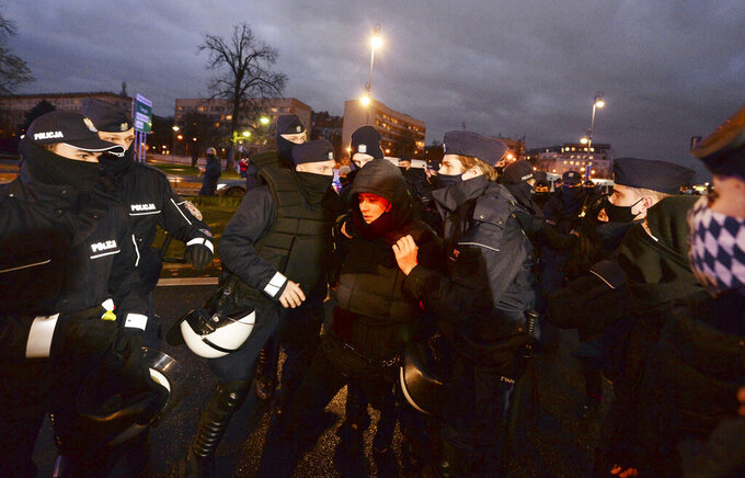 Police confront protesters in front of the Education Ministry building in Warsaw, Poland, on Monday Nov. 23, 2020. Police detained several people as women-led protests over abortion rights flared up in Warsaw and elsewhere in Poland. The protests, organized by the group Women's Strike, have been occurring regularly since the constitutional court issued an Oct. 22 ruling that further tightens an abortion law that was already one of the most restrictive in Poland.(AP Photo/Czarek Sokolowski)