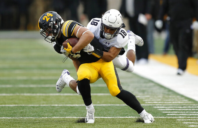 Iowa wide receiver Nick Easley tries to break a tackle by Northwestern defensive back Cameron Ruiz (18) after making a reception during the first half of an NCAA college football game, Saturday, Nov. 10, 2018, in Iowa City, Iowa. (AP Photo/Charlie Neibergall)