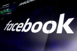FILE - In this March 29, 2018, file photo, the logo for Facebook appears on screens at the Nasdaq MarketSite, in New York's Times Square. Aleksandr Kogan, the data scientist at the center of Facebook's Cambridge Analytica privacy scandal, said he is dropping a defamation lawsuit against the social network rather than engage in an expensive, drawn-out legal battle. (AP Photo/Richard Drew, File)