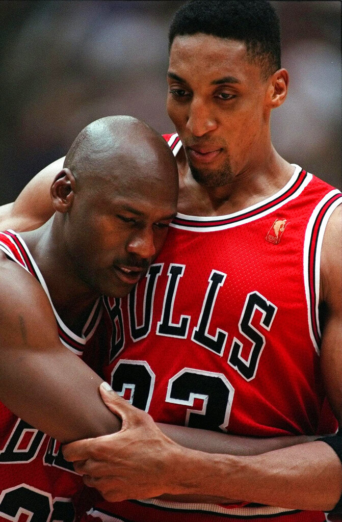 FILE - In this June 11, 1997 file photo, Chicago Bulls Scottie Pippen, right, embraces an exhausted Michael Jordan following their win in Game 5 of the NBA Finals against the Utah Jazz, in Salt Lake City. The flu-like illness Jordan fought through to lead the Bulls to a crucial victory in the 1997 NBA Finals created instant fodder for the virtue of perseverance. Pushing past boundaries, overcoming obstacles and adversity —  that is part of the ethos of major competitive sports. That is how elite athletes become wired to win. (AP Photo/Jack Smith, File)
