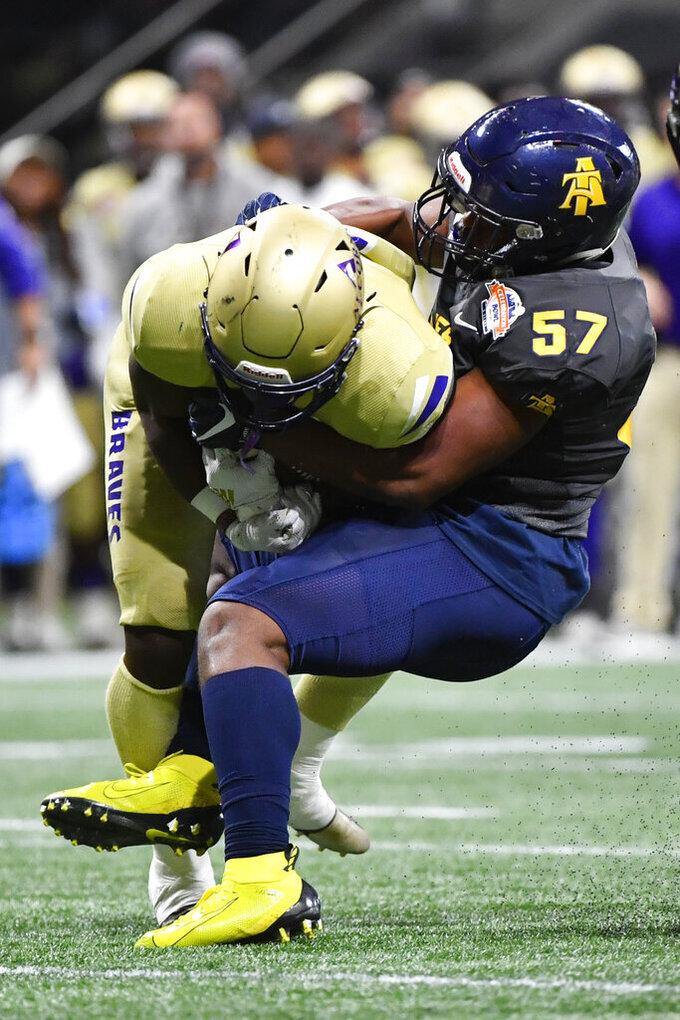 North Carolina A&T linebacker Jacob Roberts (57) brings down Alcorn State tight end Jerimiah Green during the first half of the Celebration Bowl NCAA college football game, Saturday, Dec. 21, 2019, in Atlanta. (John Amis/Atlanta Journal-Constitution via AP)