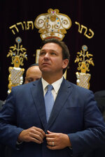 Florida Gov. Ron DeSantis buttons his jacket after speaking, Monday, June 14, 2021, at the Shul of Bal Harbour, a Jewish community center in Surfside, Fla. DeSantis visited the South Florida temple to denounce anti-Semitism and stand with Israel, while signing a bill into law that would require public schools in his state to set aside moments of silence for children to meditate or pray. (AP Photo/Wilfredo Lee)