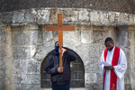 Christians, one carrying a cross, pray during the Good Friday procession after walking in the Via Dolorosa near the Church of the Holy Sepulchre, traditionally where many Christians believe Jesus Christ was crucified, buried and rose from the dead, in Jerusalem's Old City, Friday, April 2, 2021. (AP Photo/Ariel Schalit)