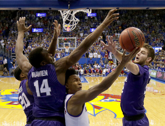 Kansas' Devonte' Graham shoots under pressure from Kansas State's Dean Wade, right, Xavier Sneed (20) and Makol Mawien (14) during the first half of an NCAA college basketball game Saturday, Jan. 13, 2018, in Lawrence, Kan. (AP Photo/Charlie Riedel)