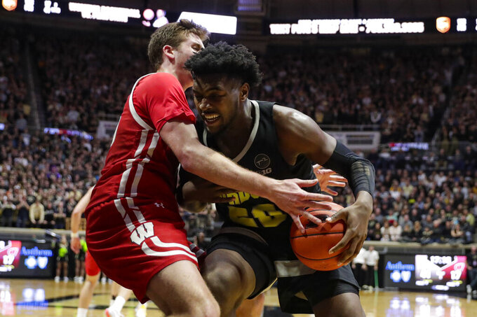 Wisconsin forward Nate Reuvers (35) ties up Purdue forward Trevion Williams (50) during the second half of an NCAA college basketball game in West Lafayette, Ind., Friday, Jan. 24, 2020. (AP Photo/Michael Conroy)