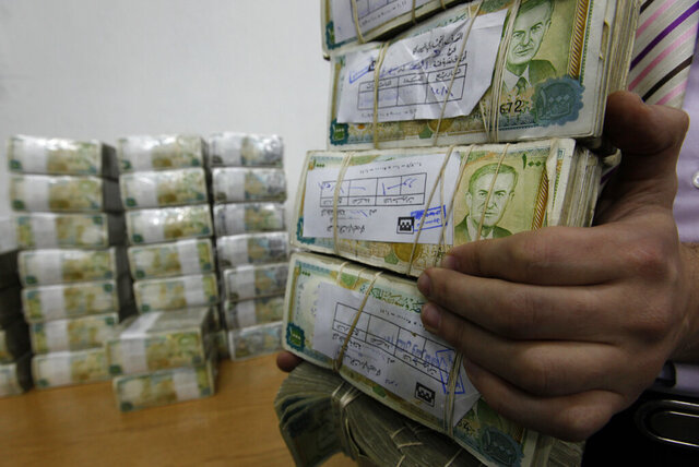 FILE - In this January 13, 2010 file photo, a Syrian employee, holds packets of Syrian currency in the Central Syrian Bank in, Damascus, Syria. With Syria's currency hitting record lows, a nationwide symbolic campaign has been launched by merchants, barbers, supermarkets and even gyms to support the Syrian pound. (AP Photo/Hussein Malla, File)