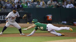 Detroit Tigers third baseman Dawel Lugo, left, waits to tag out Oakland Athletics' Matt Chapman (26) during the first inning of a baseball game Friday, Sept. 6, 2019, in Oakland, Calif. (AP Photo/Ben Margot)