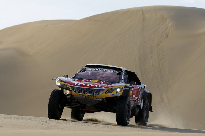 Driver Stephane Peterhansel, of France, and co-driver Jean Paul Cottret, of France, race their Peugeot during the 5th of the 2018 Dakar Rally between San Juan de Marcona and Arequipa, Peru, Wednesday, Jan. 10, 2018. (AP Photo/Ricardo Mazalan)