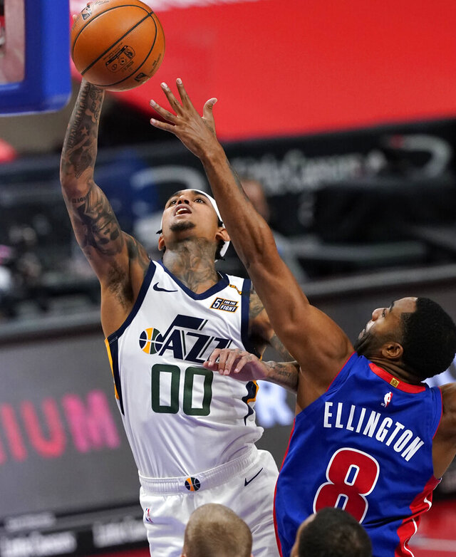Detroit Pistons guard Wayne Ellington (8) attempts to block a shot by Utah Jazz guard Jordan Clarkson (00) during the first half of an NBA basketball game, Sunday, Jan. 10, 2021, in Detroit. (AP Photo/Carlos Osorio)