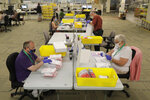 Workers process ballots from Tuesday's primary election that were mailed out and then deposited in drop boxes or mailed back in, Wednesday, Aug. 5, 2020, at the King County Elections headquarters in Renton, Wash., south of Seattle. Washington state has offered voting by mail since 2011. (AP Photo/Ted S. Warren)