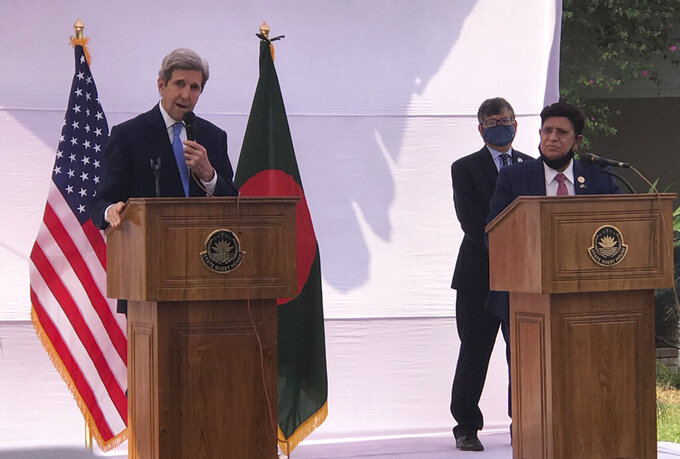 John Kerry, the special U.S. envoy on climate, speaks with Bangladeshi Foreign Minister A.K. Abdul Momen standing beside him in Dhaka, Bangladesh, Friday, April 9, 2021. Kerry said Friday that President Joe Biden was keen to work with Bangladesh in dealing with climate change impacts after the United States' return to the Paris accord. (AP Photo/Al-emrun Garjon)