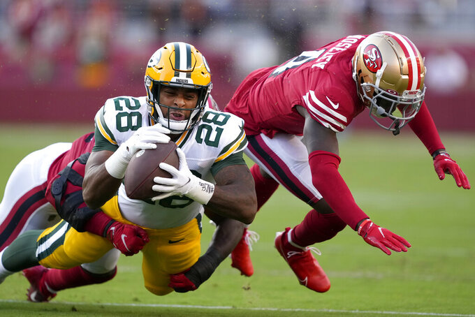 Green Bay Packers running back A.J. Dillon (28) is tackled by San Francisco 49ers linebacker Azeez Al-Shaair, rear, and defensive back Emmanuel Moseley during the first half of an NFL football game in Santa Clara, Calif., Sunday, Sept. 26, 2021. (AP Photo/Tony Avelar)