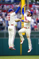 Philadelphia Phillies right fielder Bryce Harper, right, and first baseman Rhys Hoskins celebrate after the Phillies won a baseball game against the New York Yankees, Sunday, June 13, 2021, in Philadelphia. (AP Photo/Matt Slocum)