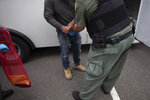 FILE - In this July 8, 2019, file photo, a U.S. Immigration and Customs Enforcement (ICE) officers transfer a man in handcuffs and ankle cuffs onto a van during an operation in Escondido, Calif. Advocacy groups and unions are pressuring Marriott, MGM and others not to house migrants who have been arrested by U.S. Immigration and Customs Enforcement agents. But the U.S. government says it sometimes needs bed space, and if hotels don't help it might have to split up families. (AP Photo/Gregory Bull, File)