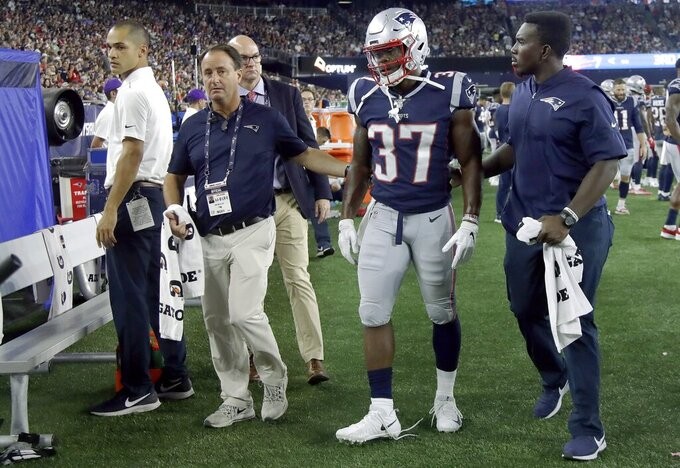 New England Patriots running back Damien Harris (37) is escorted on the sideline after an injury in the first half of an NFL preseason football game against the Carolina Panthers, Thursday, Aug. 22, 2019, in Foxborough, Mass. (AP Photo/Elise Amendola)