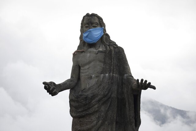 A protective face mask adorns a Jesus Christ statue as a reminder for residents to wear masks as a precaution against the spread of the new coronavirus, in the Petare neighborhod in Caracas, Venezuela, Friday, July 17, 2020. (AP Photo/Ariana Cubillos)