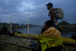 Migrants bound for the U.S.-Mexico border wait on a bridge that stretches over the Suchiate River, connecting Guatemala and Mexico, in Tecun Uman, Guatemala, early Saturday, Oct. 20, 2018. The entry into Mexico via the bridge has been closed. The migrants have moved about 30 feet back from the gate that separates them from Mexican police to establish a buffer zone. About 1,000 migrants now remain on the bridge between Guatemala and Mexico. (AP Photo/Moises Castillo)