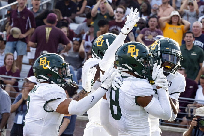 FILE - In this Saturday, Sept. 4, 2021, file photo, Baylor's JT Woods, right, celebrates with safety Jalen Pitre, center right, and other teammates after returning an interception for a touchdown during the first half of an NCAA college football game Texas State in San Marcos, Texas. Baylor's defense had three interceptions in the season opener .AP Photo/Michael Thomas)