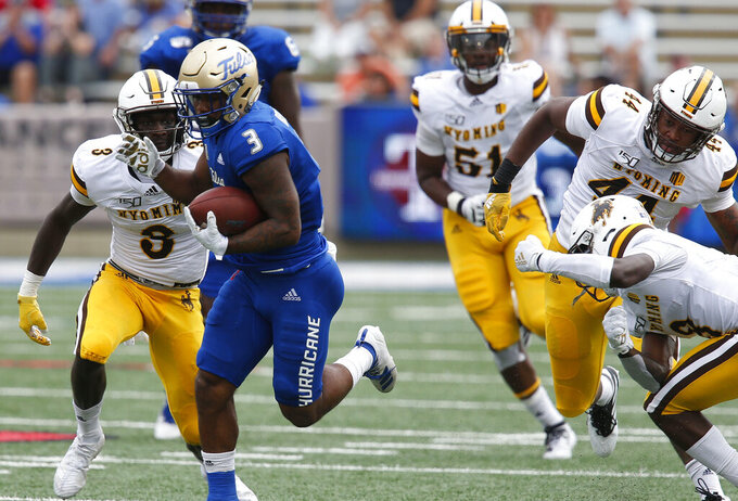Tulsa's Shamari Brooks breaks tackles by Wyoming defenders during  an NCAA college football game Saturday, Sept. 21, 2019, in Tulsa, Okla. (Stephen Pingry/Tulsa World via AP)