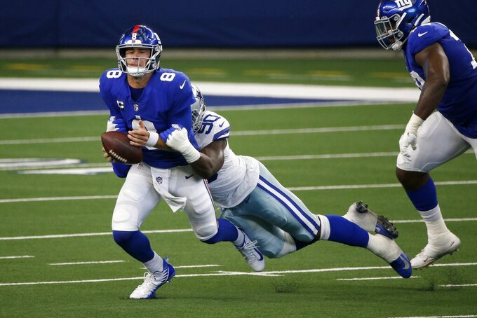 Dallas Cowboys defensive end DeMarcus Lawrence (90) sacks and strips the ball away from New York Giants quarterback Daniel Jones (8) in the first half of an NFL football game in Arlington, Texas, Sunday, Oct. 11, 2020. The Cowboys' Anthony Brown (30) recovered the ball and returned it for a touchdown. (AP Photo/Michael Ainsworth)