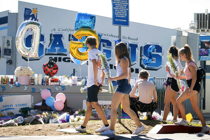High school students bring flowers to a memorial, Monday, Nov. 18, 2019, for two students killed during a shooting at Saugus High School in Santa Clarita, Calif., several days earlier. The students will return to school on Dec. 2. (Sarah Reingewirtz/The Orange County Register via AP)