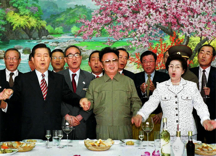 FILE - In this June 15, 2000, file photo, from left in front row; former South Korean President Kim Dae-jung,  former North Korean leader Kim Jong Il, and former South Korean First Lady Lee Hee-ho, hold hands as they sing a song titled