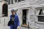 Artist Ryan Mendoza walks in front of the house of U.S. civil rights campaigner Rosa Parks, which he rebuilt for public display, in Naples, Italy, Tuesday, Sept. 15, 2020. The rundown, paint-chipped Detroit house where Parks took refuge after her famous bus boycott is on display in a setting that couldn't be more incongruous: the imposing central courtyard of the 18th century Royal Palace. (AP Photo/Gregorio Borgia)