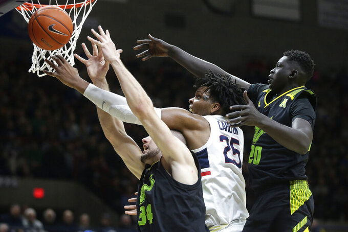 Connecticut's Josh Carlton, center, vies for a rebound with South Florida's Antun Maricevic, left, of Croatia, and Mayan Kiir, right, during the second half of an NCAA college basketball game, Sunday, March 3, 2019, in Storrs, Conn. (AP Photo/Steven Senne)