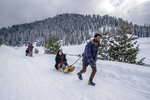 """Kashmiris pull Indian tourists on sledges at Gulmarg, northwest of Srinagar, Indian controlled Kashmir, Saturday, Jan. 9, 2021. Snow this winter has brought along with it thousands of locals and tourists to Indian-controlled Kashmir's high plateau, pastoral Gulmarg, which translates as """"meadow of flowers."""