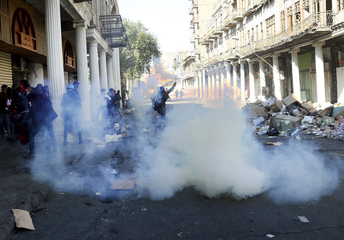 Riot police fire tear gas while blocking al-Rashid Street during clashes with anti-government demonstrators in Baghdad, Iraq, Friday, Nov. 22, 2019. Iraq's massive anti-government protest movement erupted Oct. 1 and quickly escalated into calls to sweep aside Iraq's sectarian system. Protesters occupy several Baghdad squares and parts of three bridges in a standoff with security forces. (AP Photo/Hadi Mizban)JA