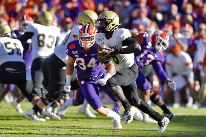Wofford quarterback Joe Newman rushes out of the backfield during the first half of an NCAA college football game against Clemson, Saturday, Nov. 2, 2019, in Clemson, S.C. (AP Photo/Richard Shiro)