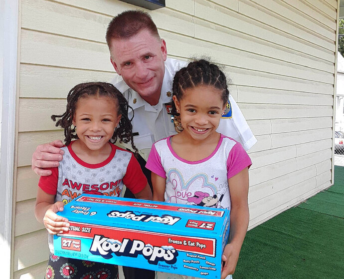 In this July 20, 2020 photo provided by Erica Dantzler, Jayden Dantzler-Clay, 5, and his sister Amiyah Dantzler-Clay, 6, hold a box of ice pops with police officer Maj. Richard Gibson at their home in Baltimore. The siblings gave a grape-flavor ice pop to the officer as he worked in their neighborhood on a hot summer day. Two days later, Maj. Gibson came back to return the favor. (Erica Dantzler via AP)
