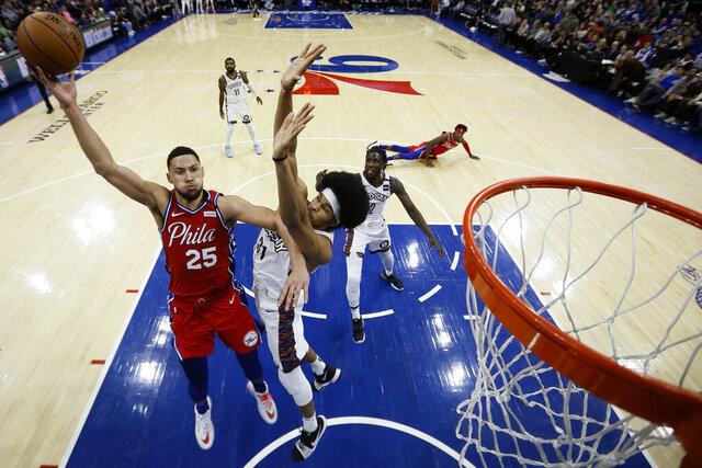 Philadelphia 76ers' Ben Simmons, left, goes up for a shot against Brooklyn Nets' Jarrett Allen during the second half of an NBA basketball game, Wednesday, Jan. 15, 2020, in Philadelphia. (AP Photo/Matt Slocum)