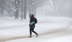 A pedestrian makes her way across empty Speer Blvd. as a storm packing snow and high winds sweeps in over the region Tuesday, Nov. 26, 2019, in Denver. Stores, schools and government offices were closed or curtailed their hours while on another front, Thanksgiving Day travellers were forced to wrestle with snow-packed roads and flight delays or cancellations throughout the intermountain West. (AP Photo/David Zalubowski)