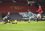 Liverpool's Mohamed Salah, center, scores his side's fourth goal during the English Premier League soccer match between Manchester United and Liverpool, at the Old Trafford stadium in Manchester, England, Thursday, May 13, 2021. (Peter Powell/Pool via AP)