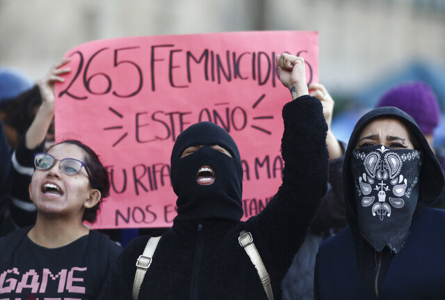 Women shout during a protest against gender violence outside the National Palace that includes the presidential office and residence, in Mexico City, Tuesday, Feb. 18, 2020. The killing of a 7-year-old girl on the southern outskirts of Mexico City has stoked rising anger over the brutal slayings of women, including one found stabbed to death and skinned earlier this month. (AP Photo/Eduardo Verdugo)