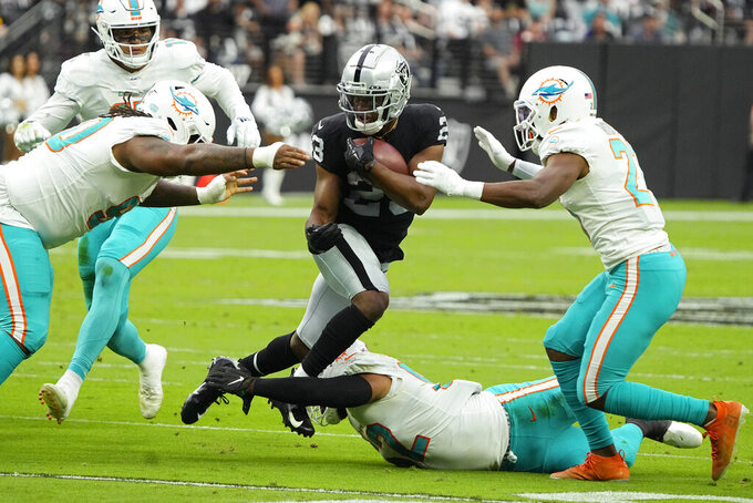 Las Vegas Raiders running back Kenyan Drake (23) runs for a gain against the Miami Dolphins during the first half of an NFL football game, Sunday, Sept. 26, 2021, in Las Vegas. (AP Photo/Rick Scuteri)