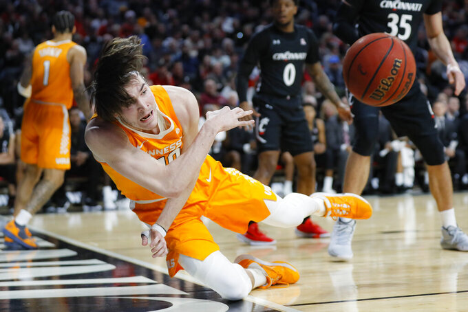 Tennessee's John Fulkerson (10) dives to inbound a loose ball during the first half of an NCAA college basketball game against Cincinnati, Wednesday, Dec. 18, 2019, in Cincinnati. (AP Photo/John Minchillo)