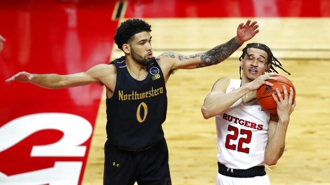 Northwestern's Boo Buie (0) defends against Rutgers' Caleb McConnell (22) during the first half of an NCAA college basketball game in Piscataway, N.J., Saturday, Feb. 13, 2021. (AP Photo/Noah K. Murray)