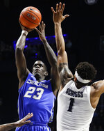 Creighton's Damien Jefferson (23) shoots against Xavier's Paul Scruggs (1) during the first half of an NCAA college basketball game Wednesday, Feb. 13, 2019, in Cincinnati. (AP Photo/John Minchillo)