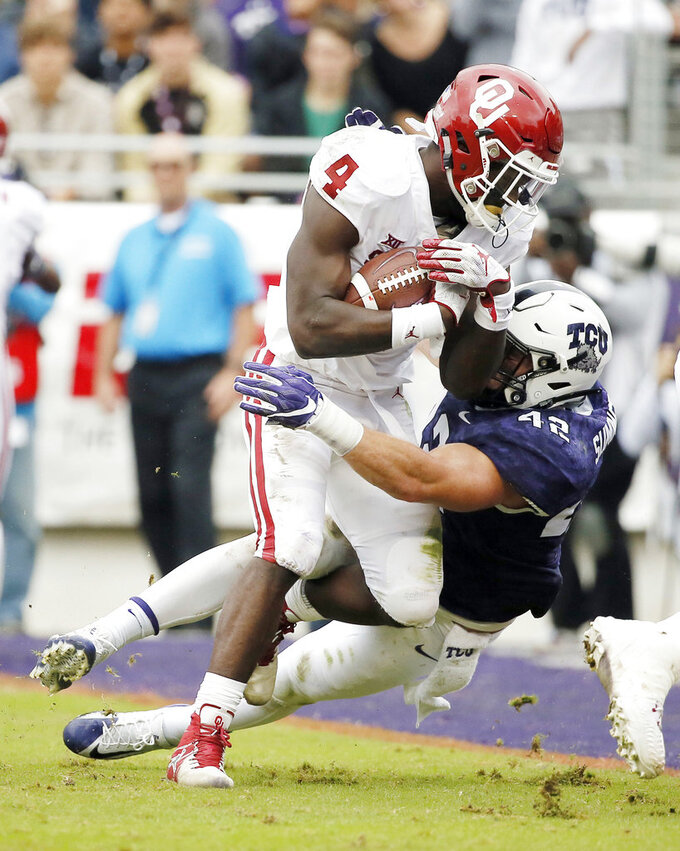 Oklahoma running back Trey Sermon (4) battles past TCU linebacker Ty Summers (42) to score a touchdown in the first half of an NCAA college football game, Saturday, Oct. 20, 2018, in Fort Worth, Texas. (AP Photo/Brandon Wade)
