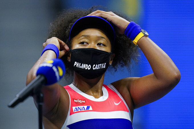 Naomi Osaka, of Japan, adjusts her mask after defeating Jennifer Brady, of the United States, during a semifinal match of the US Open tennis championships, Thursday, Sept. 10, 2020, in New York. (AP Photo/Seth Wenig)