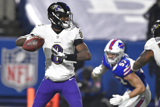 Baltimore Ravens quarterback Lamar Jackson (8) throws a pass as Buffalo Bills' A.J. Epenesa (57) rushes him during the first half of an NFL divisional round football game Saturday, Jan. 16, 2021, in Orchard Park, N.Y. (AP Photo/Adrian Kraus)