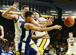 Penn State's Myreon Jones passes the ball under pressure from Iowa's Ryan Kriener, left, and Cordell Pemsl during the first half of an NCAA college basketball game, Saturday, Feb. 29, 2020, in Iowa City, Iowa. (AP Photo/Cliff Jette)