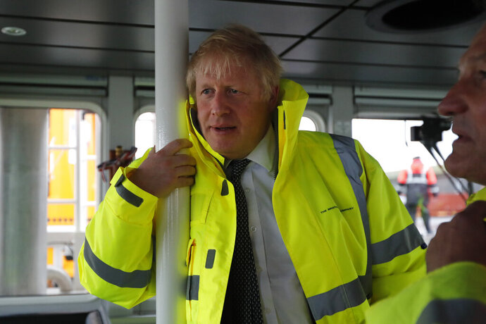 Britain's Prime Minister Boris Johnson looks out from the steering cabin of tug boat during a General Election campaign trail stop in the port of Bristol, England, Thursday, Nov. 14, 2019. Britain goes to the polls on Dec. 12. (AP Photo/Frank Augstein, Pool)