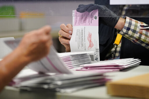 FILE - In this a Clark County election department facility Oct. 31, 2020, file photo, County employees process mail-in ballots in Las Vegas. Nevada lawmakers are considering sending mail-in ballots to all active voters in future elections after passing a law last summer that directed election officials to do so to prevent the coronavirus from spreading at polling places. A legislative committee is scheduled on Thursday, April 1, 2021, to hear a proposal to make the policy permanent. (AP Photo/John Locher, File)