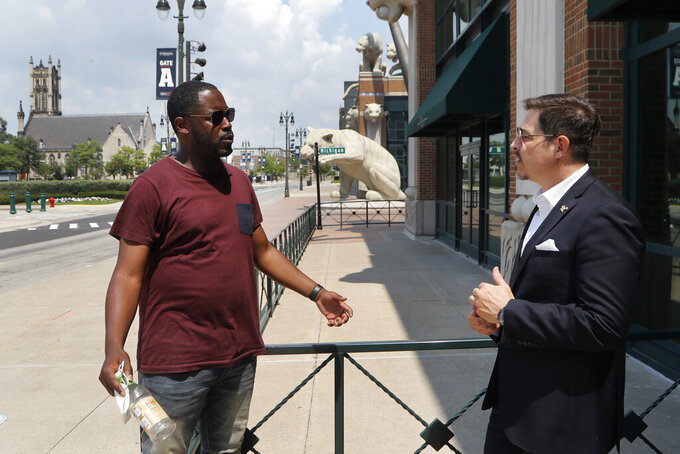"""Kenny Valentino, left, manager of Delmar, a rooftop business in Greektown, and Adrian Tonon, the 24-Hour Economy Ambassador for Detroit Mayor Mike Duggan, talk, Wednesday, July 8, 2020, in Detroit. Bars and restaurants in the area are desperately hoping people come watch games in nearly empty ballparks on TV in establishments as packed as possible with social distancing guidelines. """"The real fans will still want to come out and be around other fans and not just watch the games at home,"""" Valentino said. (AP Photo/Carlos Osorio)"""